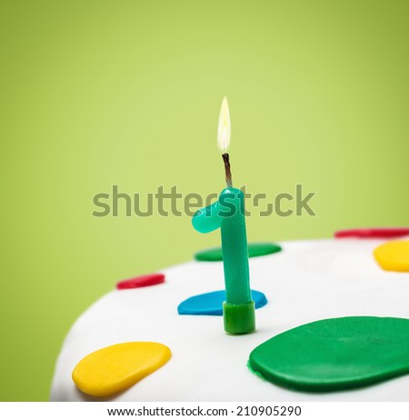 Burning candle with the number one on a birthday cake - stock photo