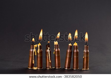Burning candles and empty rifle cartridges. As a symbol of war and victims. Located on black cardboard as a background. - stock photo