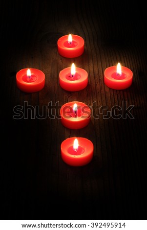 burning  candles arranged in a cross, shallow dof