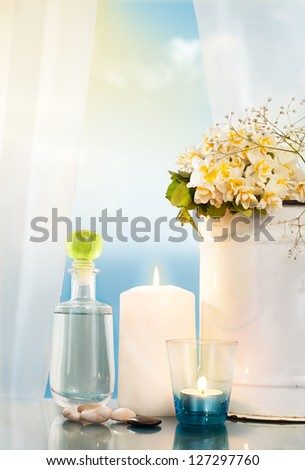 burning candles, bucket and a bottle in front of a window with open curtain with sky and sea in background - stock photo