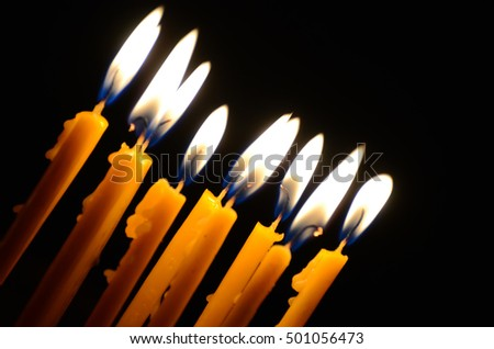 Burning candles in a church on a dark background