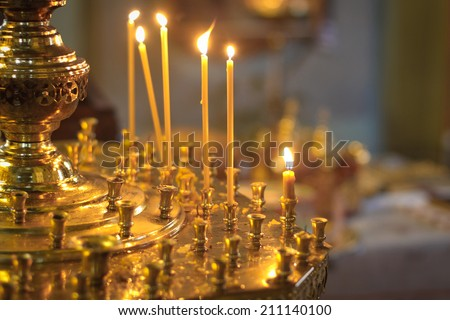 Burning candles in a Russian ortodox church. Close-up of ordinary church interior. Selective focus. - stock photo