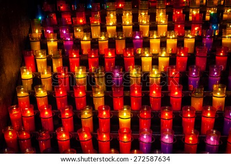 burning candles in candlesticks of different color on an altar in Catholic church - stock photo