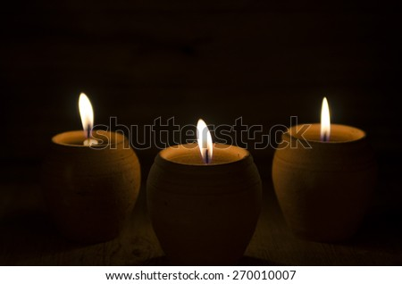 Burning candles in pot on black background