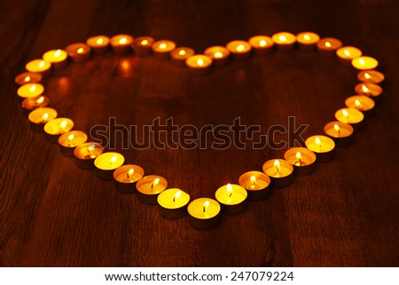 Burning candles in shape of heart on dark background - stock photo