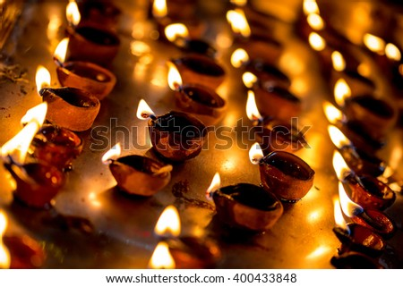Burning candles in the Indian temple. Diwali the festival of lights. Warning - authentic shooting with high iso in challenging lighting conditions. A little bit grain and blurred motion effects. - stock photo