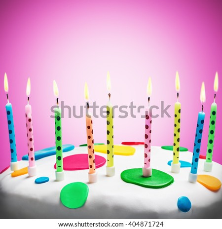 burning candles on a birthday cake on purple background