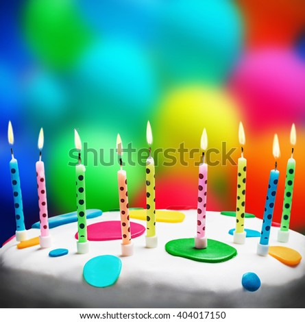 burning candles on a birthday cake on the background of balloons - stock photo