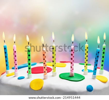 burning candles on a birthday cake on the color background