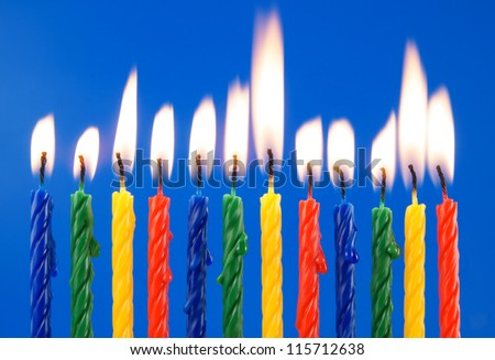 Burning candles on blue background - stock photo