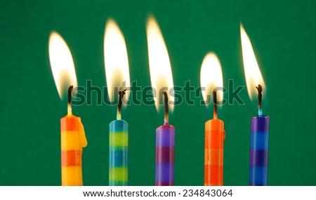 Burning candles on green background  - stock photo