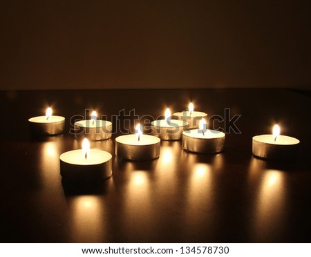 Burning candles on the dark wooden table. Selective focus - stock photo