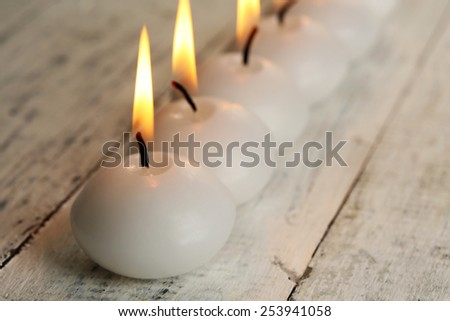 Burning candles on wooden table close-up - stock photo