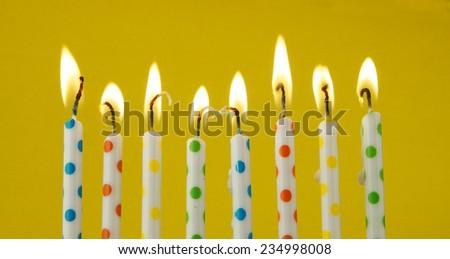 Burning candles on yellow background  - stock photo