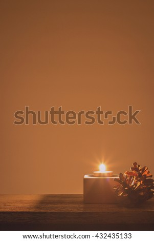 Burning candles with pine cones on wooden background.