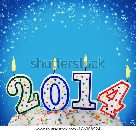 burning candles with the symbol of the new year on the cake - stock photo