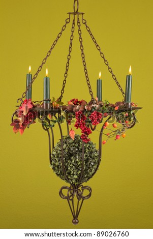 Burning candlestick with fall decoration and a green background - stock photo