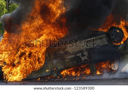 Burning car with large flames and black smoke - stock photo