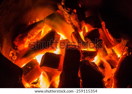 Burning charcoal in stove on dark background
