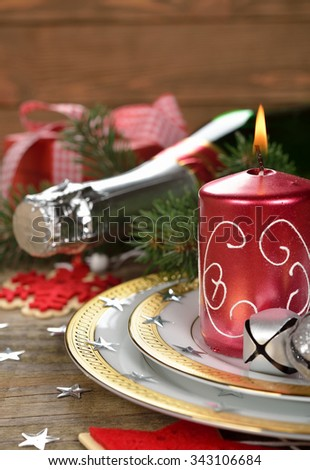 Burning Christmas candle and plate on a wooden background