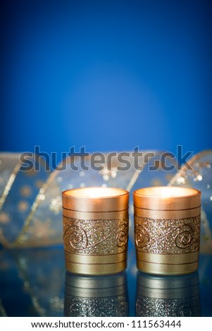 Burning Christmas candles and gold ribbon on blue background