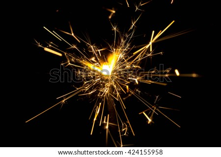 burning christmas fire sparklers on black background - stock photo