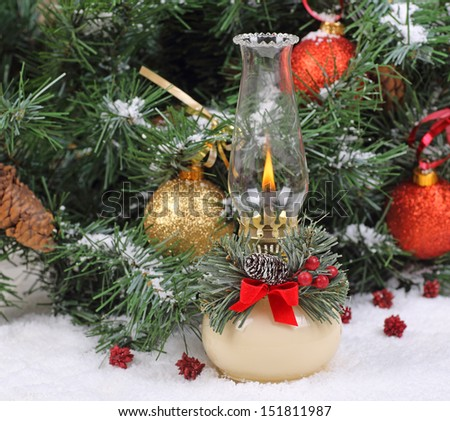 Burning Christmas lamp with decorated tree in background