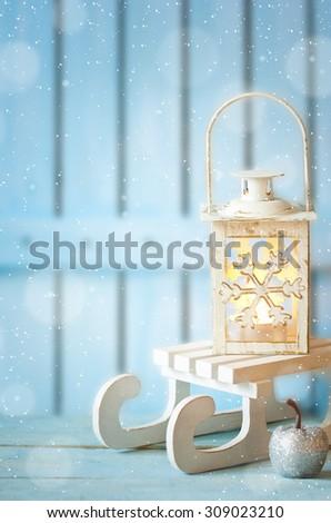 Burning christmas lantern on white sled and christmas decoration on blue wooden background. Christmas card. - stock photo