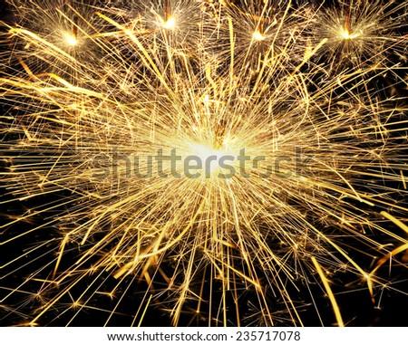 burning christmas sparklers on black background - stock photo