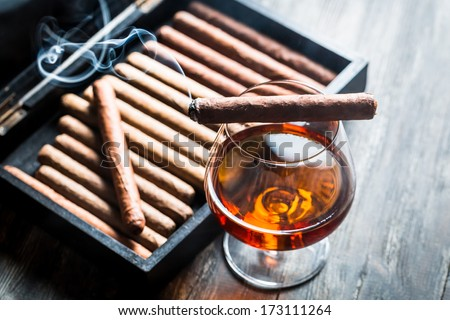 Burning cigar on humidor and cognac in glass - stock photo