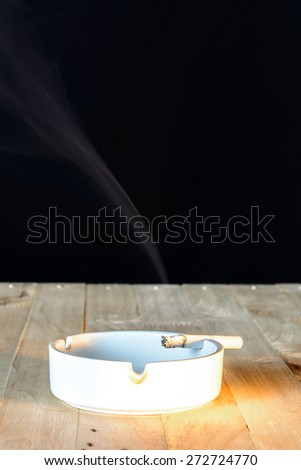 Burning cigarette in ashtray on wooden table and black background - stock photo