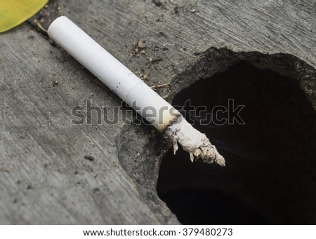Burning cigarette on the ground