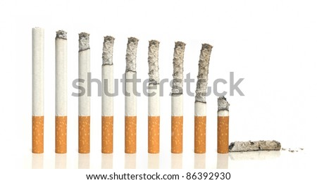 Burning cigarettes in a row on white background - stock photo