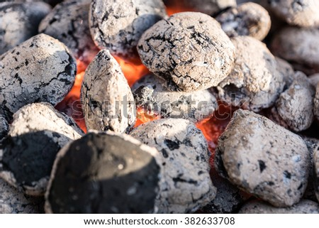 Burning coals in a barbecue grill - selected focus, narrow depth of field - stock photo