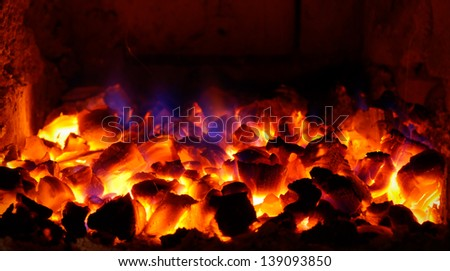 burning coals with blue flames - stock photo