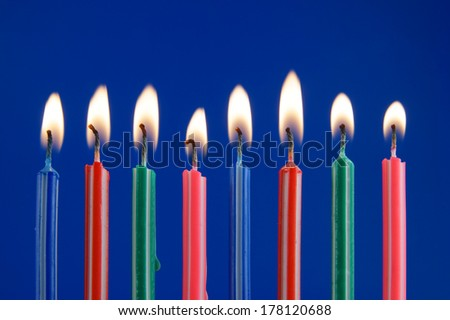 Burning colorful candles on blue background
