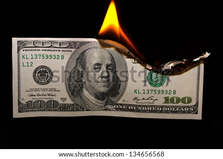 Burning dollars close up over black background - stock photo