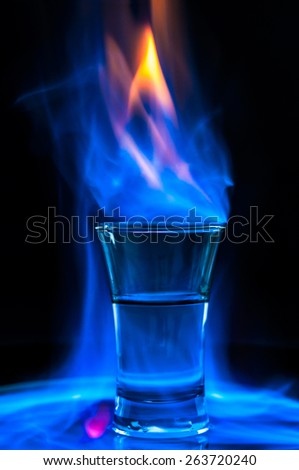Burning drink in shot glass - stock photo