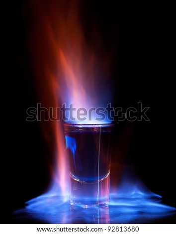 Burning drink in shot glass on a table - stock photo