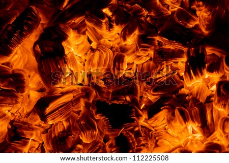 Burning embers in the dark close-up view, red textured background - stock photo