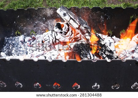 Burning embers with ash in grill - stock photo