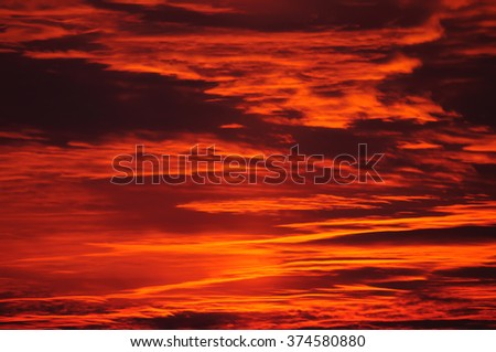 Burning evening sky at sunset. The sun is leaving the last sunbeams behind which color the heaven in dynamic illumination. - stock photo