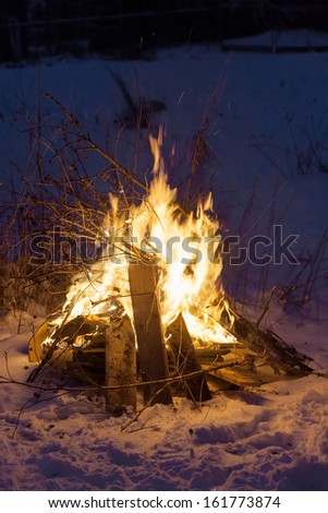 Burning fire in the winter in the Russian village - stock photo
