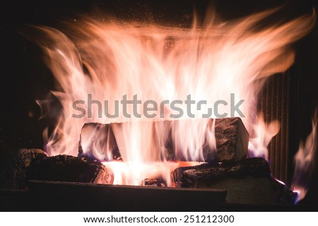 Burning fire with charcoal, firewood and fuel briquette in a fireplace in a country house  - stock photo