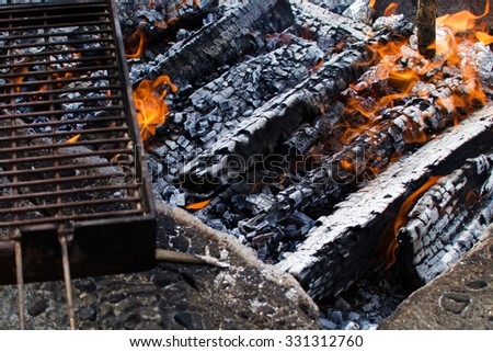 Burning fire with coals and grill for barbecue and grilling. - stock photo