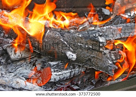 Burning firewood with ashes and flames close-up - stock photo