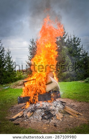 Burning furniture on a big bonfire. Forrest in the background. - stock photo