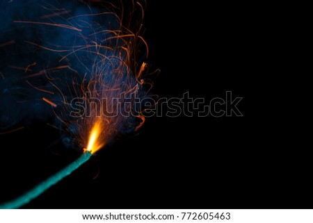 Burning fuse with sparks and blue smoke isolated on black background