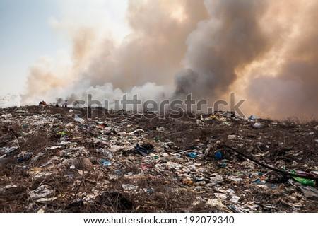 Burning garbage heap of smoke from a burning pile of garbage - stock photo