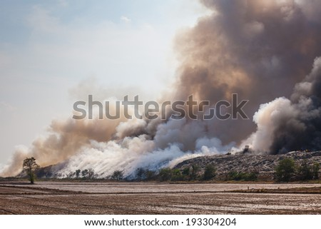 Burning garbage heap of smoke from a burning pile of garbage - stock photo